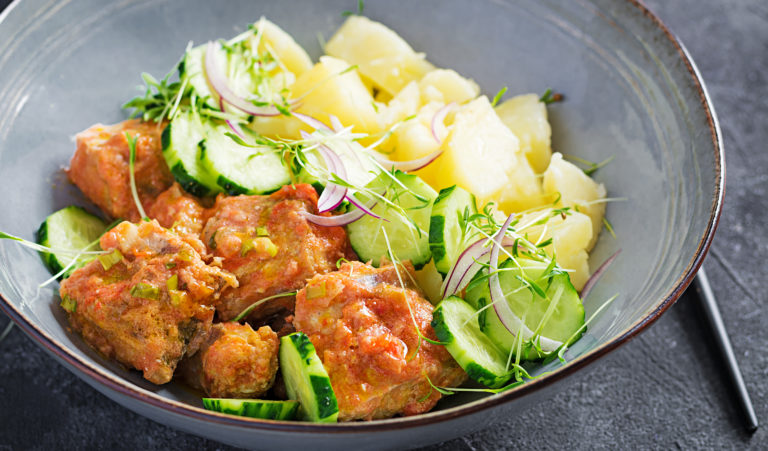 Steamed fish fillet with tomatoes sauce, boiled potatoes and fresh cucumber salad. Diet meal. Lenten food.