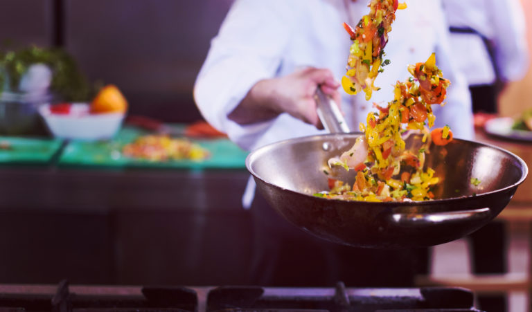 Young male chef flipping vegetables in wok at commercial kitchen
