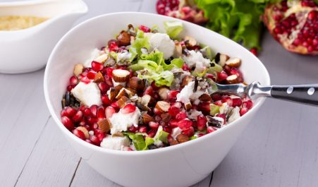 36633156 - healthy salad with pomegranate seeds, almond, feta cheese and black rice in white bowl.